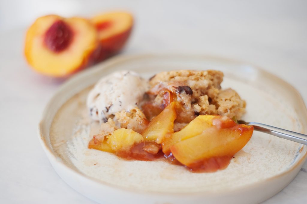 piece of fresh peach cobbler with sodelicious salted caramel ice cream